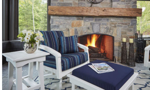 White chunky outdoor furniture with dark blue cushions and fireplace in the background, CR Plastics