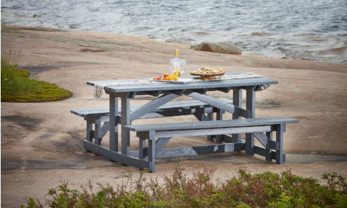 Grey harvest table with benches on a big rock by the lake, CR Plastics