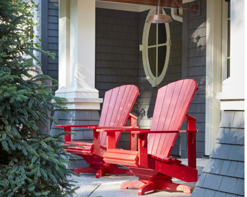 Red Adirondack Muskoka chairs on the porch of a grey and cream shingled house, CR Plastics