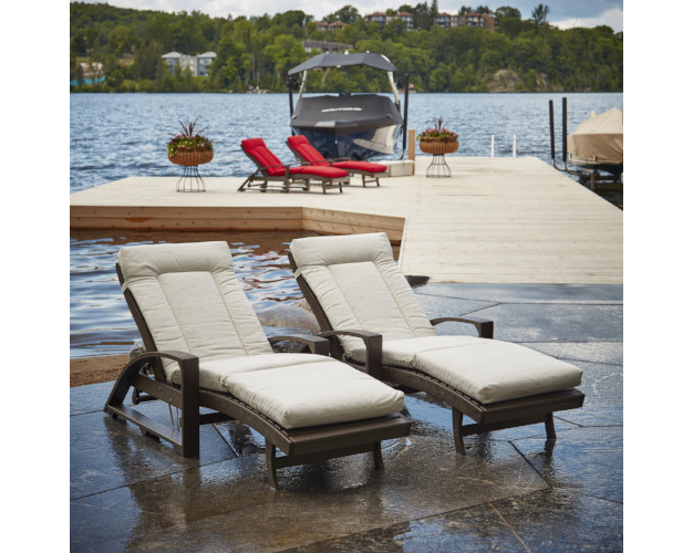 Two brown lounge chairs with cream cushions in front of dock with boat, CR Plastics