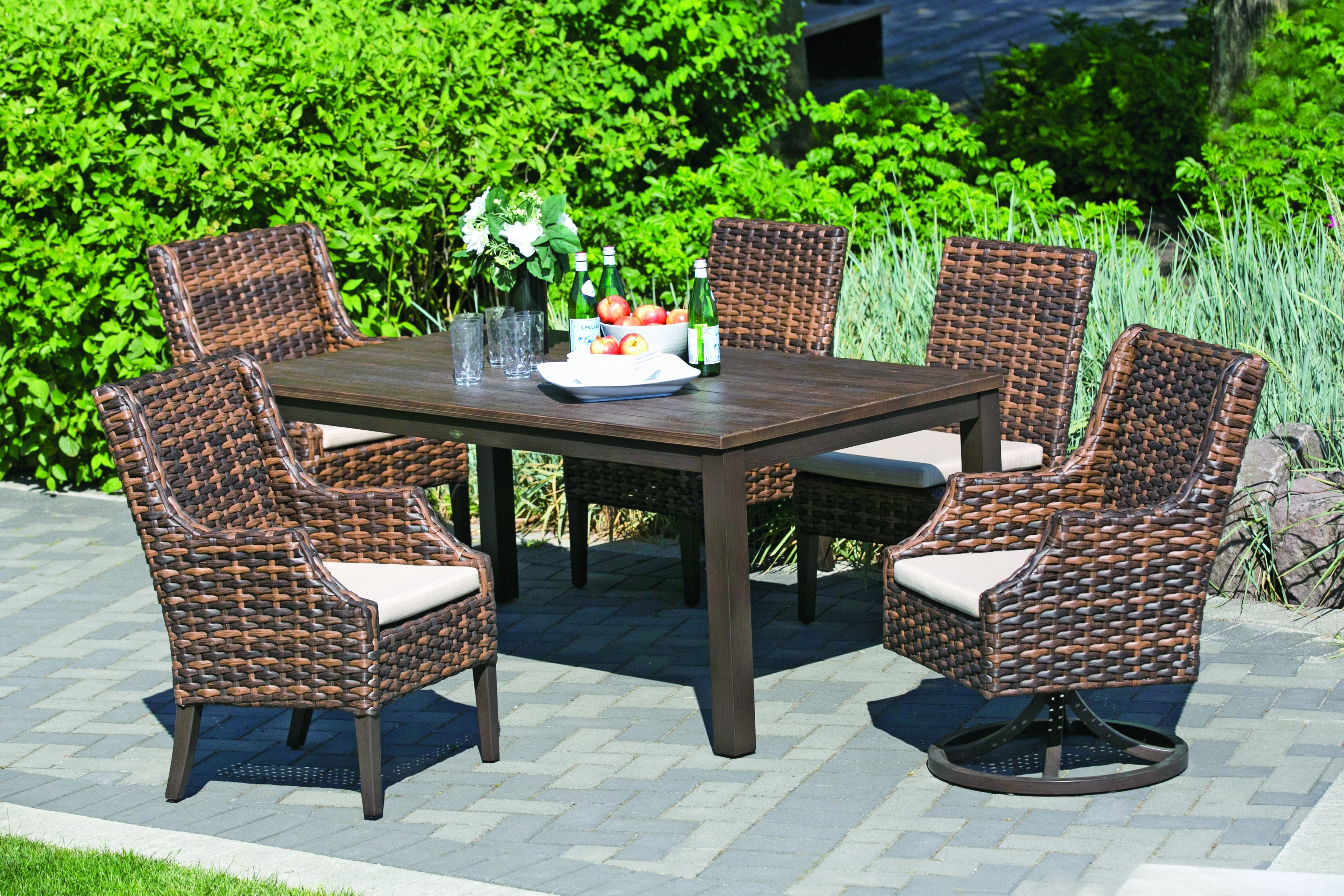 Four square rattan chairs around a dark wood table with one rattan swivel chair, Ratana