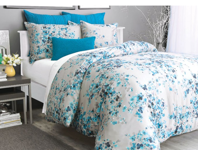 blue flowered bedding in a grey room with dark turquoise accent pillows